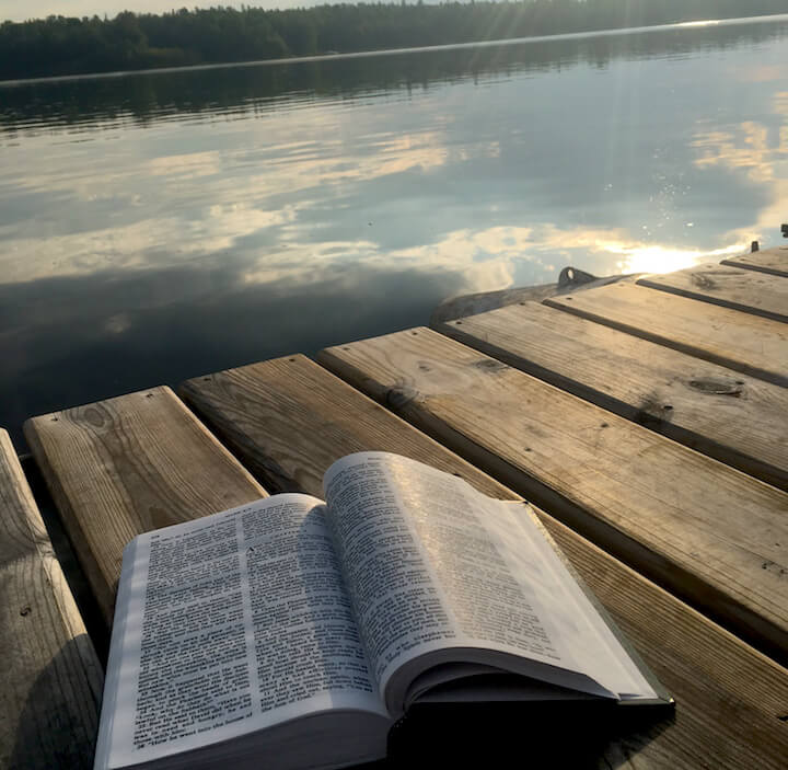 bible laying on a dock with the lake and trees in the background